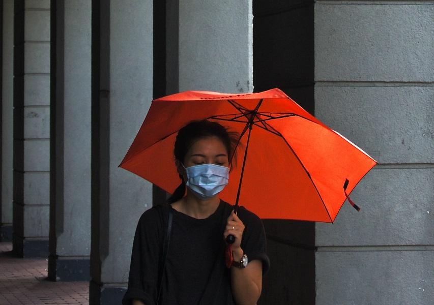 Unha muller con paraugas vermello e máscara quirúrxica